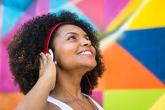 Latina woman listing to music on colorful background Stock Photos