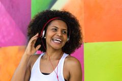 Latina woman listing to music on colorful background Royalty Free Stock Photos