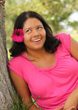 Latina Woman Rolling Her Eyes. Latina woman dressed in pink with pink flower in her hair rolling her eyes Royalty Free Stock Photo