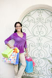 Latina Woman Shopping. Hispanic woman at iron gate with colorful magenta top and multi-colorful shopping bags Stock Photos