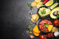 Latinamerican food party sauce guacamole, salsa, chips and ingre. Latinamerican mexican food party sauce guacamole, salsa, chips and ingredients on black table stock image