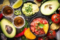 Latinamerican food party sauce guacamole, salsa, chips and tequi. Latinamerican mexican food party sauce guacamole, salsa, chips and tequila on black table. Top royalty free stock image
