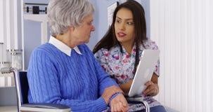 Latinamerikansk anhörigvårdare som delar minnestavlan med den äldre patienten arkivfoto
