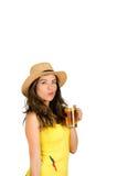 Latinamerikansk brunett som bär den gula den fotbollskjortan och hatten som poserar för kamera, medan dricka från ölexponeringsgl Arkivbild