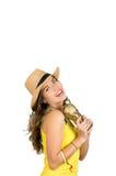 Latinamerikansk brunett som bär den gula den fotbollskjortan och hatten som poserar för kamera, medan rymma trofén, vit studiobak Arkivfoton