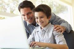 Latinamerikansk faderAnd Son Using bärbar dator arkivfoto