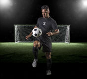 Latinamerikansk fotbollspelare som spelar fotboll på en mörk bakgrund royaltyfri foto