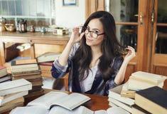 Latinamerikansk kvinna i glasögon med mycket pappers- böcker royaltyfria bilder