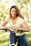 Latinamerikansk kvinna i park med cykeln Arkivbild