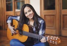 Latinamerikansk kvinna som betalar den akustiska gitarren Royaltyfri Foto
