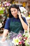Latinamerikansk kvinna som fungerar i blomsterhandlare på telefonen Arkivbilder