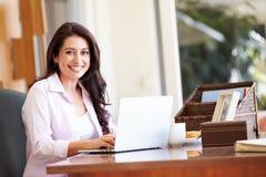 Latinamerikansk kvinna som hemma använder bärbara datorn på skrivbordet Arkivbild