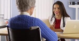 Latinamerikansk kvinnadoktor som talar med den äldre patienten arkivfoton