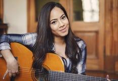 Latinamerikansk kvinnasångare som rymmer den akustiska gitarren Royaltyfri Bild