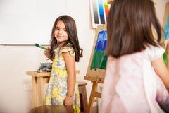 Latinamerikansk liten flicka som tycker om konstgrupp Fotografering för Bildbyråer