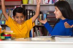 Latinamerikansk mamma och barn som firar läs- prestation Arkivbild