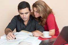 Latinamerikansk man och kvinna som hemma studerar Arkivfoton