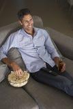 Latinamerikansk man på Sofa Watching TV Royaltyfri Foto