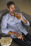 Latinamerikansk man på Sofa Watching TV Royaltyfri Fotografi