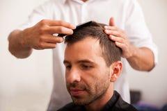 Latinamerikansk man som får en frisyr royaltyfri fotografi
