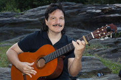 Latinamerikansk man som spelar den akustiska gitarren utomhus Arkivfoton