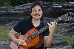 Latinamerikansk man som spelar den akustiska gitarren utomhus Arkivbild