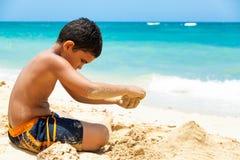 Latinamerikansk pojke som bygger ett sandslott royaltyfria bilder