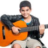 Latinamerikansk pojke som spelar en akustisk gitarr Arkivfoto