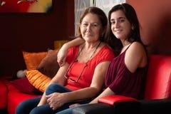 Latinamerikansk tonårs- flicka och hennes farmor hemma royaltyfria foton