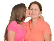 Latinamerikansk tonårs- flicka som kysser hennes farmor Arkivbilder