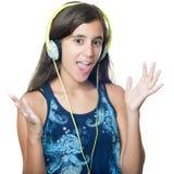 Latinamerikansk tonårs- flicka som lyssnar till musik på hennes hörlurar Arkivbild