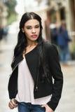 Latinamerikansk ung kvinna som bär tillfällig kläder i stads- bakgrund Royaltyfria Bilder