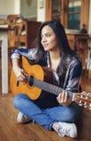 Latinamerikansk ung kvinna som spelar den akustiska gitarren arkivfoto