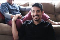 Latinamerikanska glade parinnehavhänder på soffan hemma arkivbild