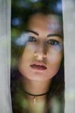 Latinamerikanska kvinnor som ser in i kameran till och med ett fönster Royaltyfri Bild