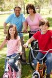 Latinamerikanska morföräldrar med barnbarn på cyklar royaltyfri foto