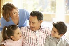 Latinamerikanska morföräldrar med barnbarn som kopplar av på Sofa At Hom royaltyfria foton