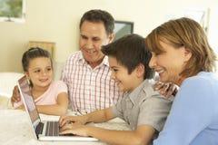 Latinamerikanska morföräldrar och barnbarn som hemma använder datoren Royaltyfria Foton