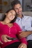 Latinamerikanska par på Sofa Watching TV tillsammans Arkivfoton