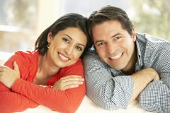 Latinamerikanska par som hemma kopplar av på soffan royaltyfria foton