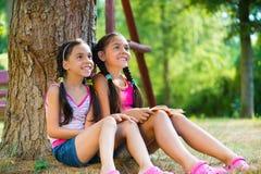 Latinamerikanska systrar som sitter under trädet och samtalet Arkivbilder