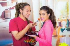 Latinamerikanska unga sunda par som tillsammans tycker om frukosten, delar frukter och ler, hem- kökbakgrund Arkivbilder