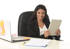 Latinamerikanskt affärskvinnasammanträde på skrivbordet för kontorsdator som ler den lyckliga användande digitala minnestavlan royaltyfri foto