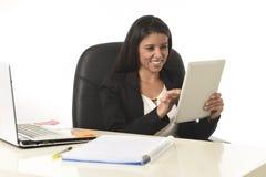 Latinamerikanskt affärskvinnasammanträde på skrivbordet för kontorsdator som ler den lyckliga användande digitala minnestavlan royaltyfria foton