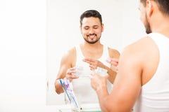 Latinamerikanskt använda för man stelnar för att utforma hans hår Arkivbild