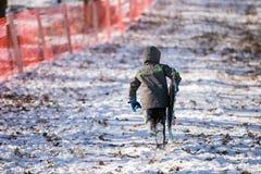 Latinamerikanskt barn som har gyckel som Sledding på snön Fotografering för Bildbyråer