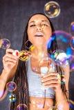 Latinen - amerikan som är kvinnlig med såpbubblor Arkivbild