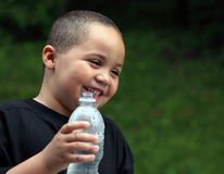Latino boy with bottle. Happy Latino boy holding a plastic water bottle Royalty Free Stock Images