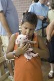 Latino boy holding baby pig Royalty Free Stock Images