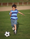 Latino boy playing with soccer ball Royalty Free Stock Image
